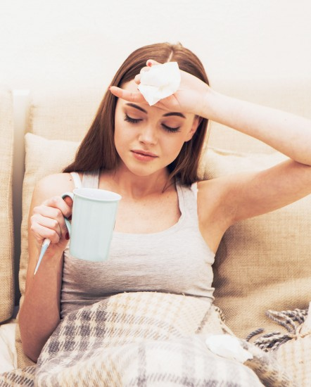 sick-woman-sitting-in-bed-with-cup-tissue-and-thermometer