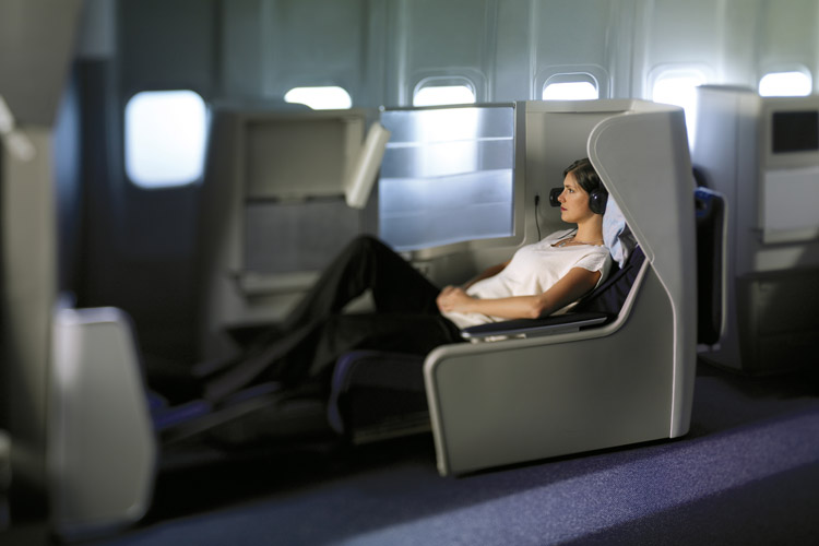 Woman reclining in spacious seat, which converts into a fully flat bed. Photo from British Airways website.